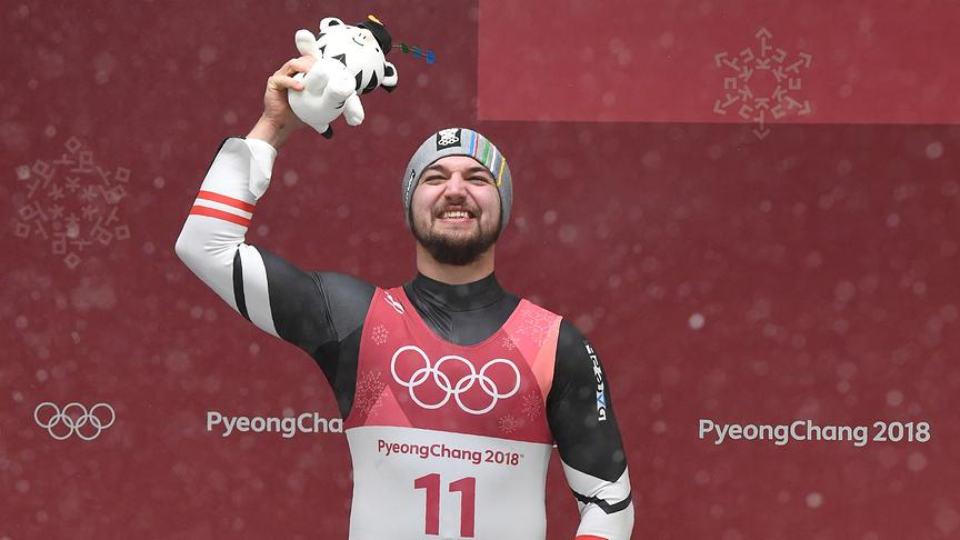 Gold medallist Austria's David Gleirscher celebrates on the podium during the victory ceremony in the men's luge singles during the Pyeongchang 2018 Winter Olympic Games, at the Olympic Sliding Centre on February 11, 2018 in Pyeongchang.